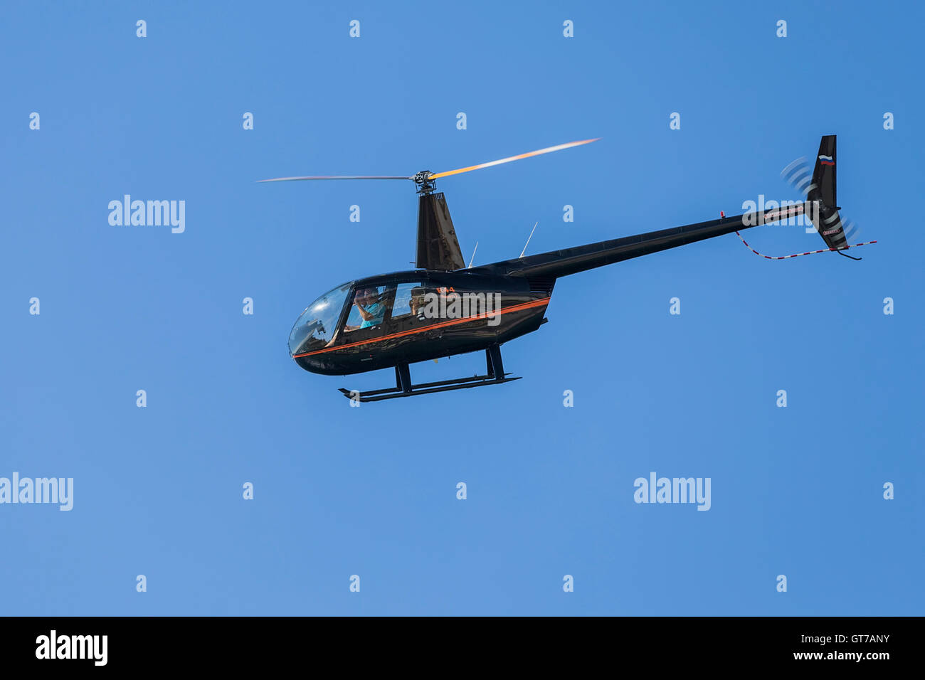 Robinson R44 Raven four seat private helicopter transports tourists - Stock Image