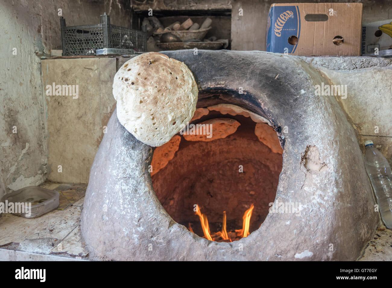 A baker uses a tandoori oven to bake fresh taftoon bread in Yazd, Iran. Stock Photo