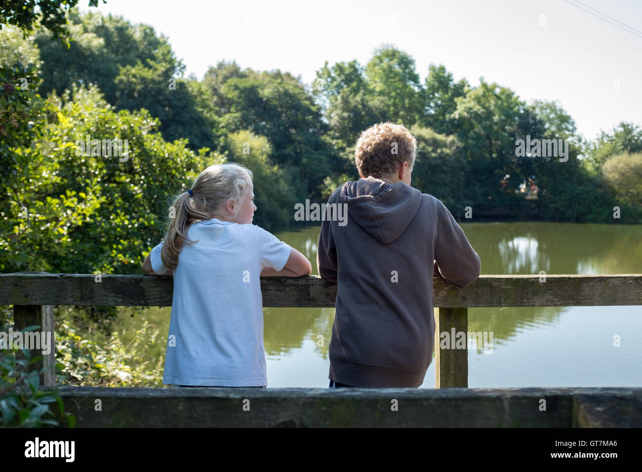 Boy and girl, brother and sister looking out over a lake in the UK countryside - Stock Image