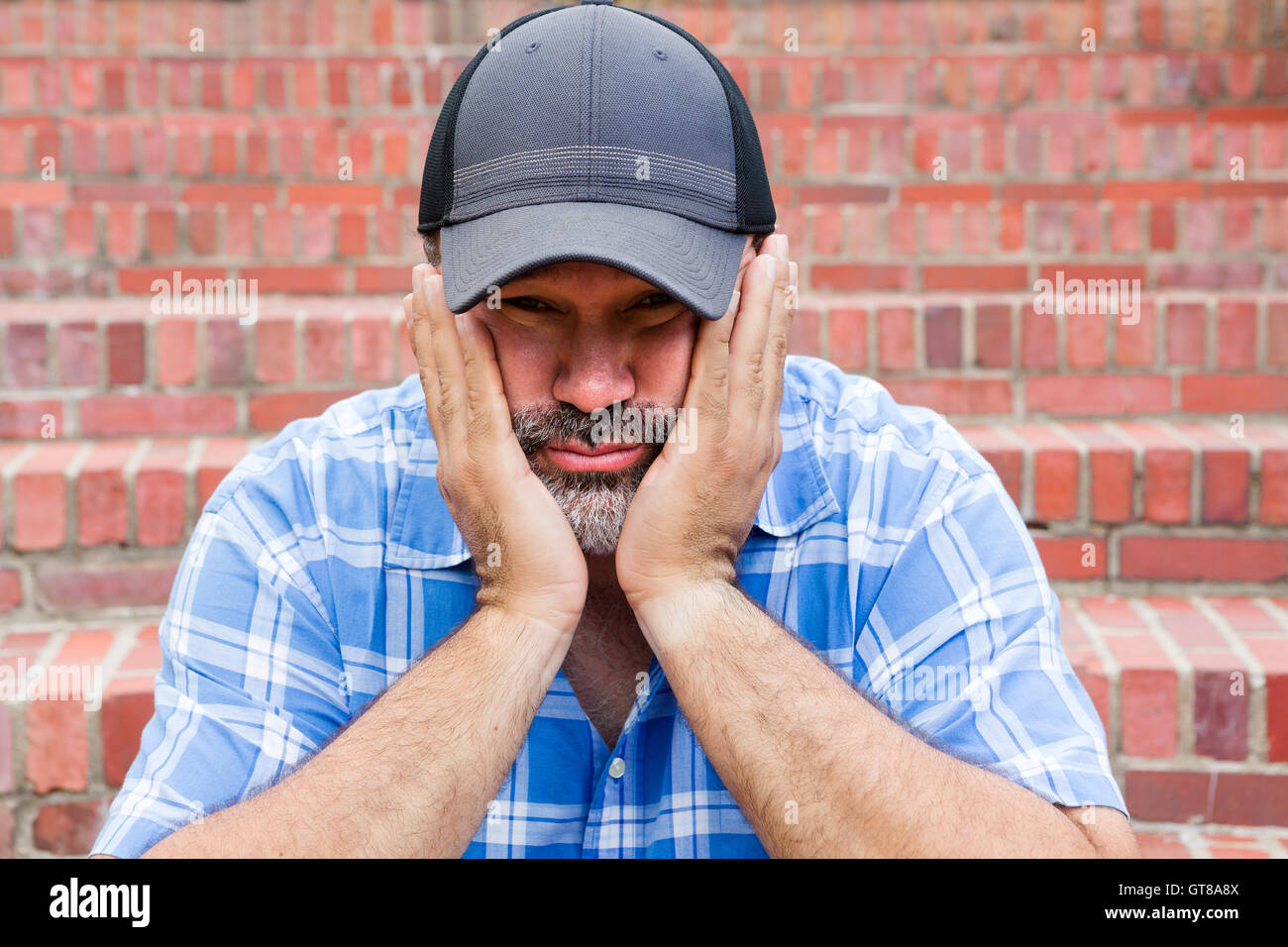 Boredom - the enemy of human happiness in a conceptual image of a middle-aged man with a goatee sitting resting - Stock Image
