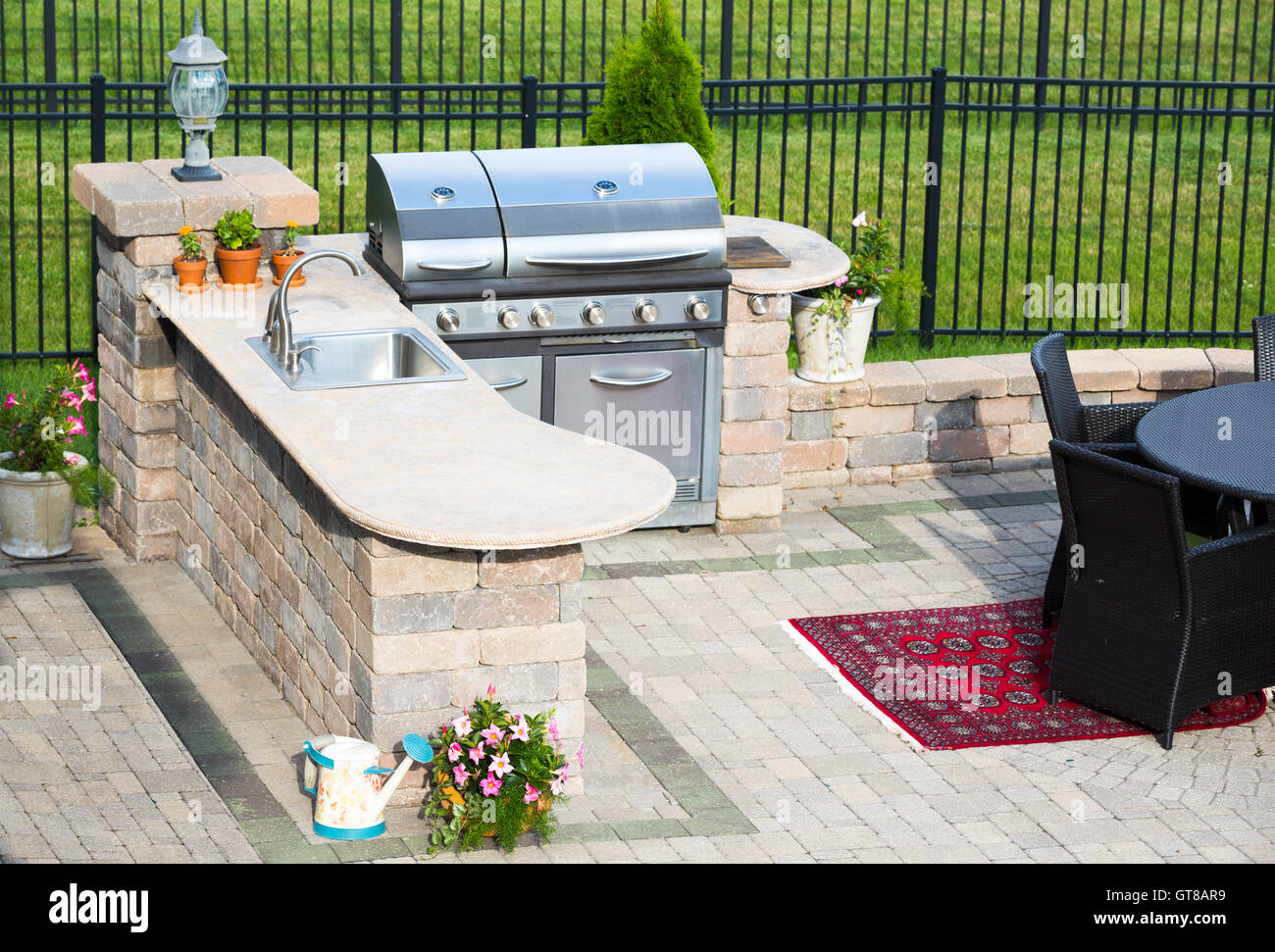 High Angle View Of A Stylish Outdoor Kitchen On A Brick Patio With A - Dining table with built in grill