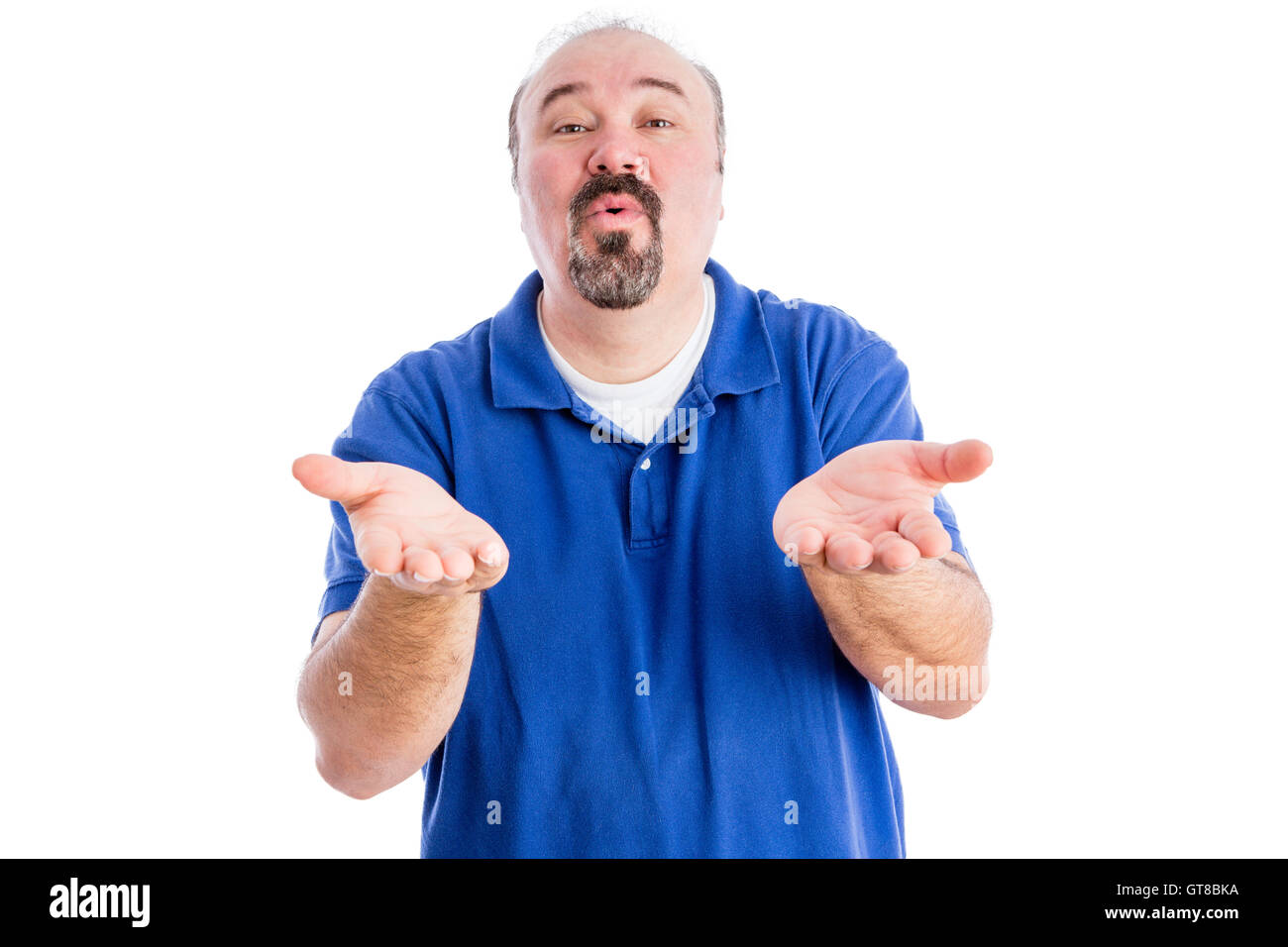 Persuasive middle-aged man with a goatee cajoling and pleading with his hands outstretched , upper body in a blue - Stock Image