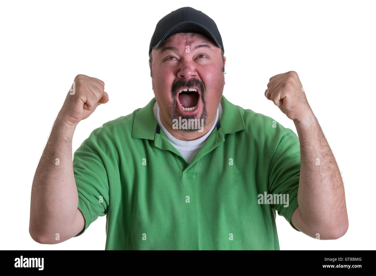 Excited Overweight Man Wearing Green Shirt and Black Baseball Cap Celebrating, Pumping Fists and Cheering in Studio - Stock Image