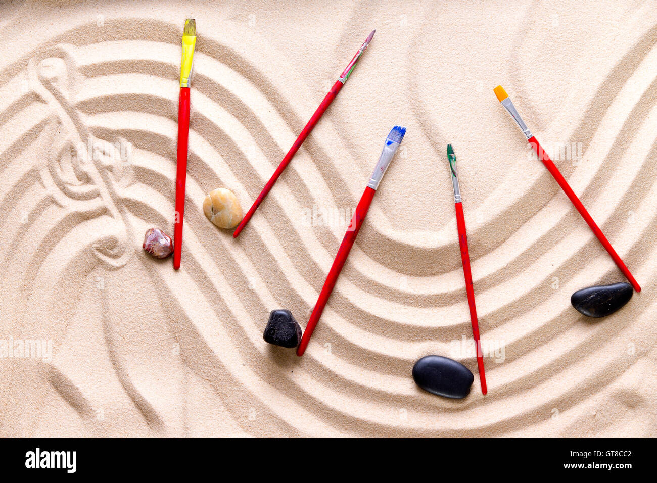 Harmony and music at the beach with an artistic conceptual image of a wavy score drawn in golden sand with a treble - Stock Image