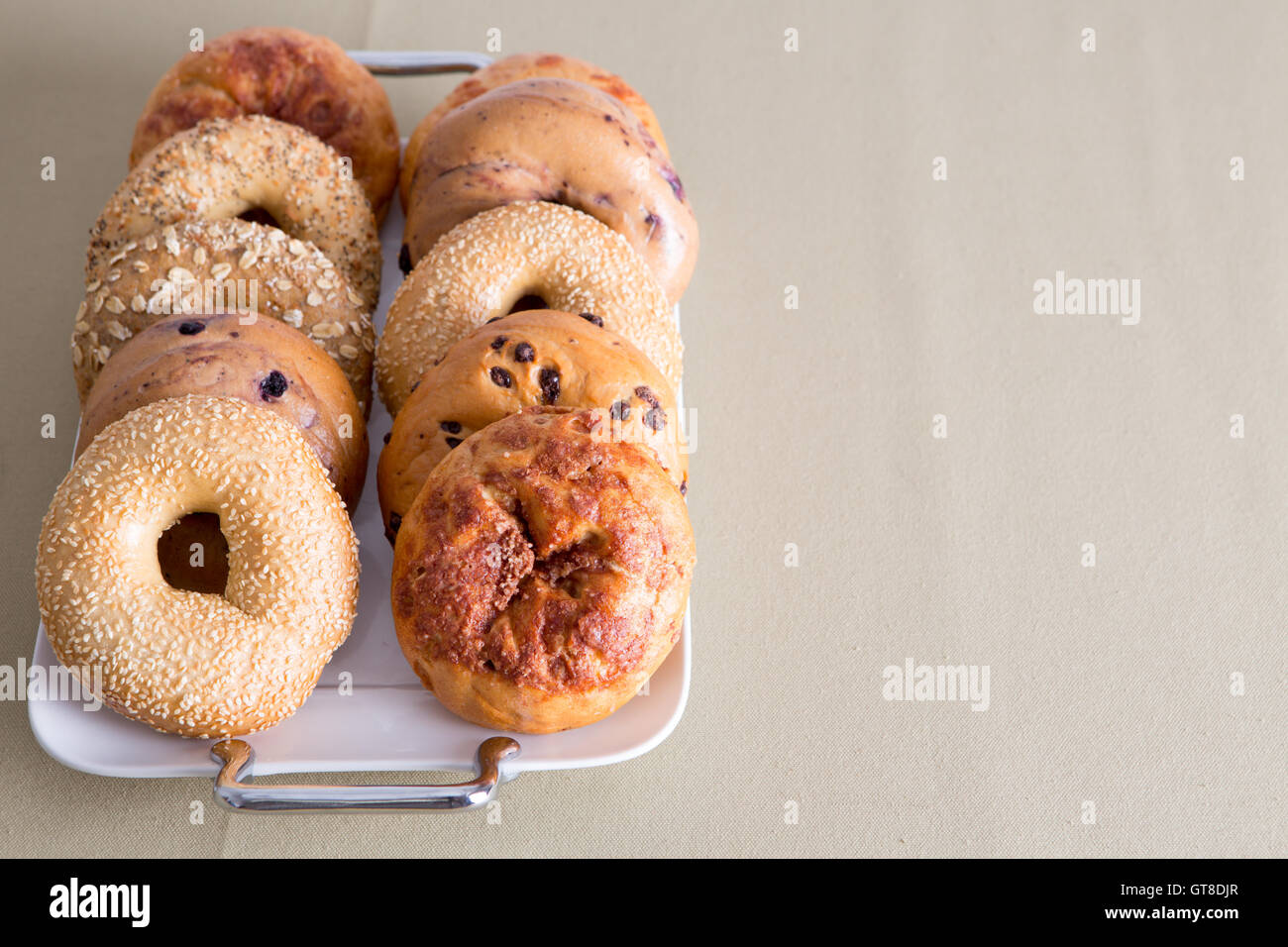 Fresh Bagel Breads, Good for After Office Meeting Snacks, Prepared on a White Tray Placed on a Table with Copy Space. - Stock Image