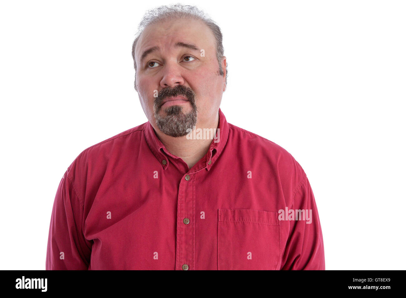 Middle-aged man with baldness and goatee beard wearing a dark red shirt while looking up to the left with a sad - Stock Image