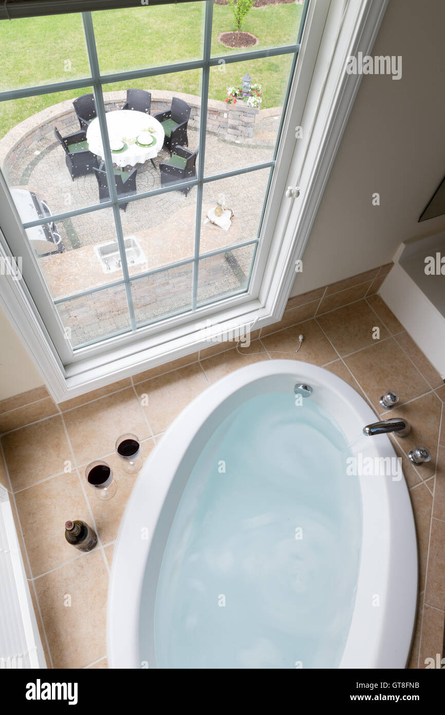 Modern sunken oval bathtub full of clean water in a brown tile Stock ...
