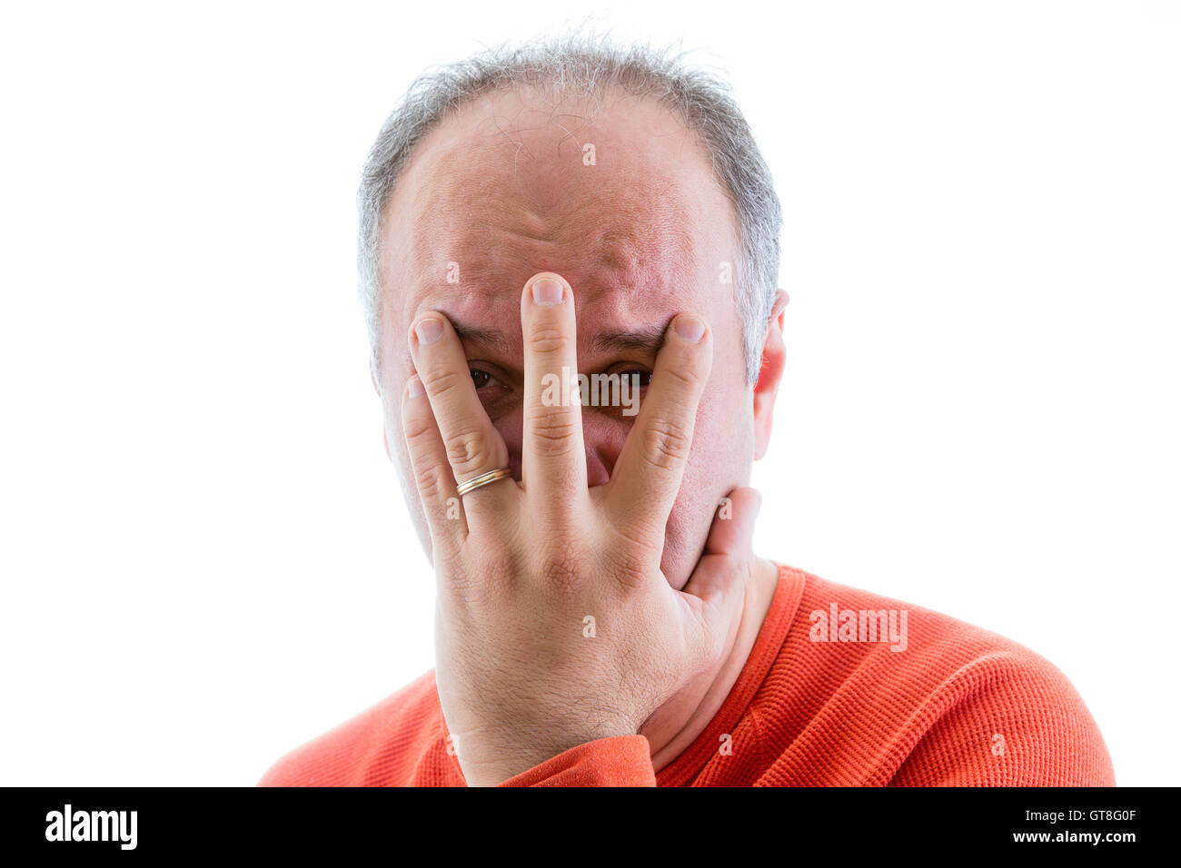 Guilty man filled with remorse hiding his face with his hand peering out between his splayed fingers, head and shoulders - Stock Image