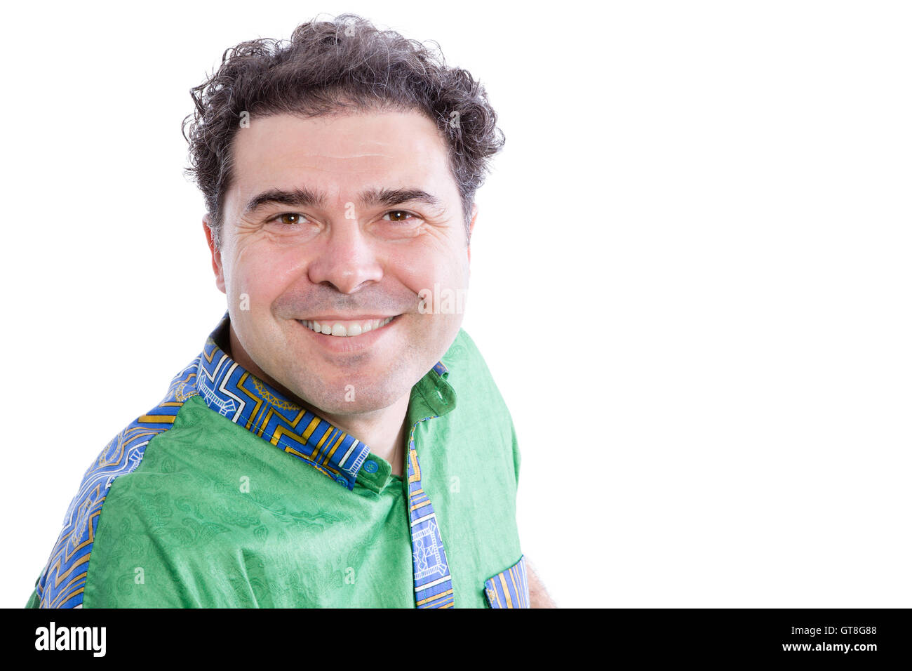 Handsome happy genuine middle-aged man leaning towards the camera with a warm friendly smile, head and shoulders - Stock Image