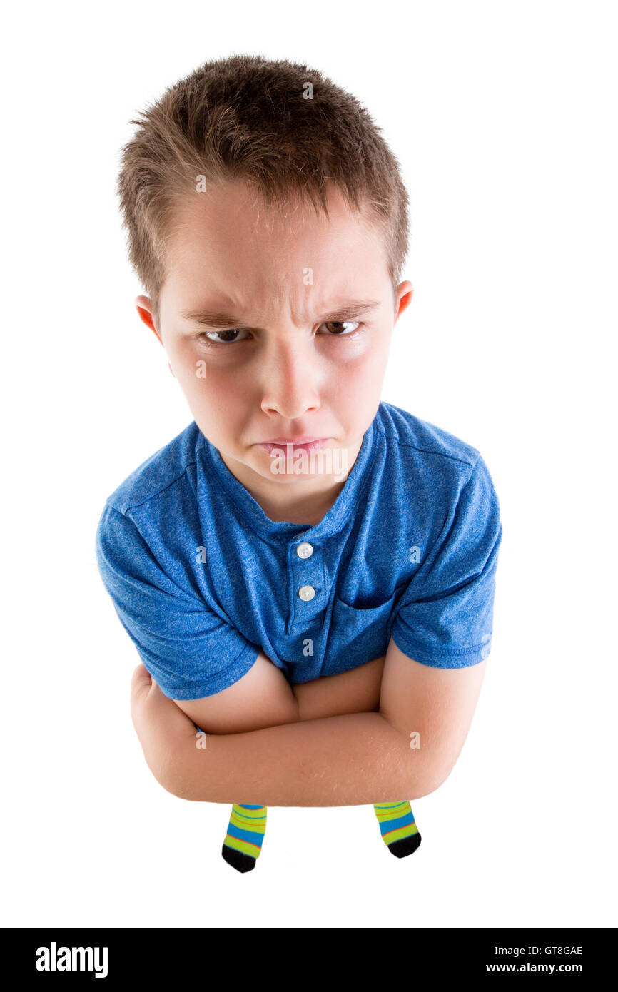 Young Boy Looking at the Camera From High Angle View with Mean Facial Expression. Isolated on White Background. - Stock Image