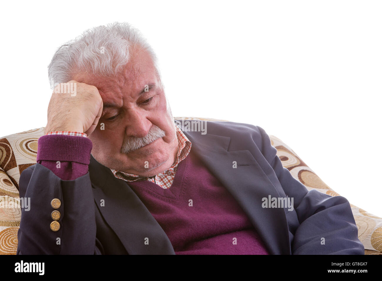 Tired elderly retired gentleman sitting thinking in a comfortable armchair resting his head on his hand with his - Stock Image