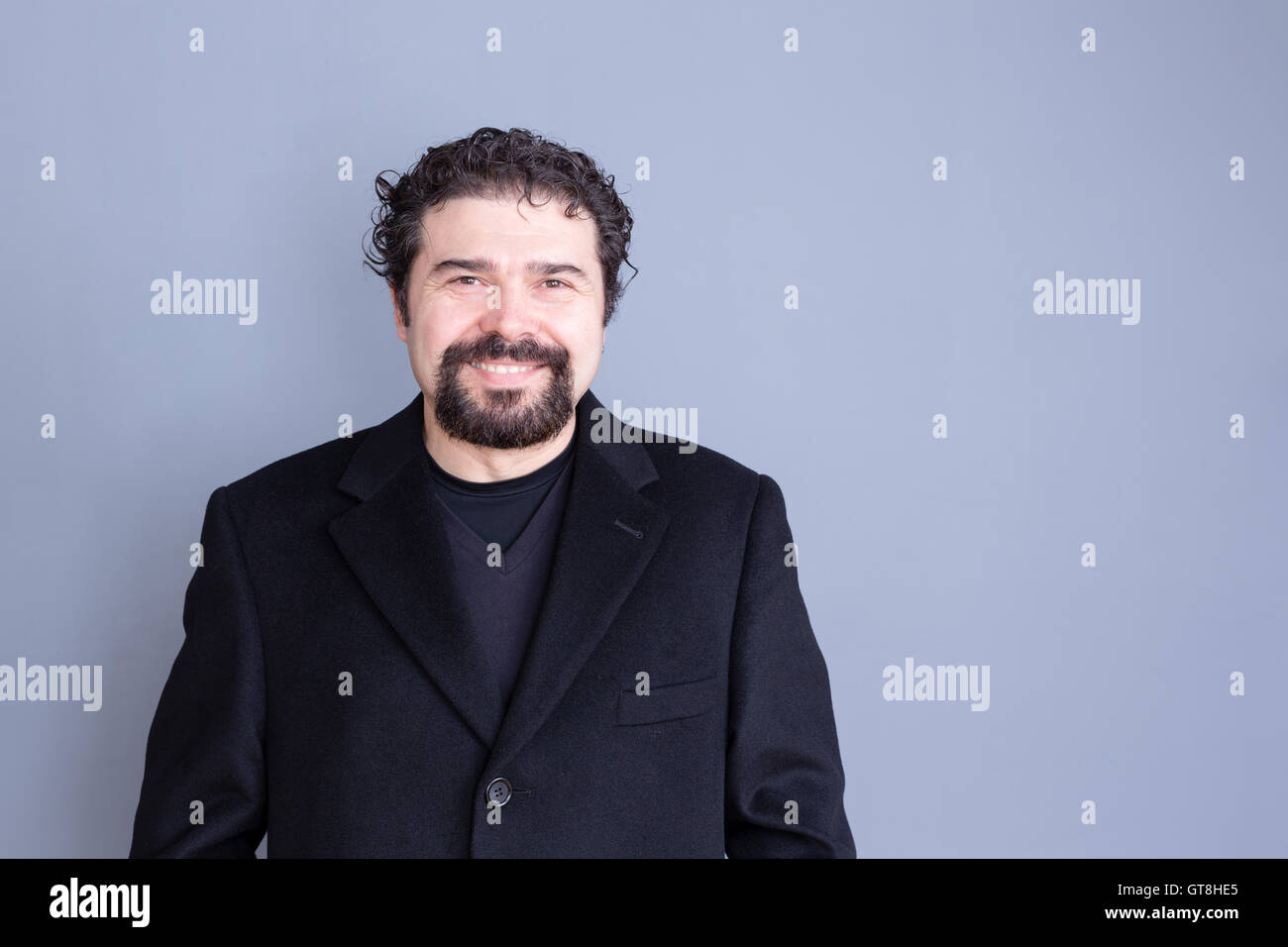 Single smiling handsome dark haired and bearded middle aged man wearing black shirt and blazer over gray background - Stock Image