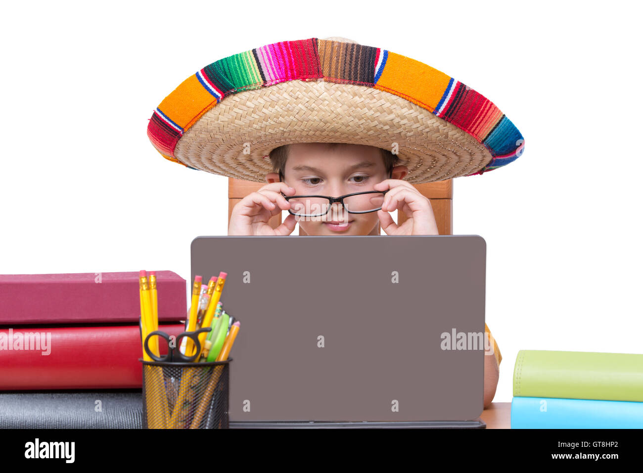 Young Boy Wearing Eyeglasses and Colorful Mexican Sombrero Hat Looking Down  at Laptop Computer Screen While Sitting at Desk Surr 6e6b013eeb6