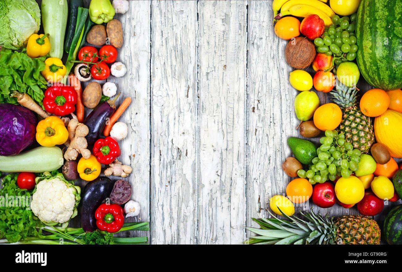 Huge group of fresh vegetables and fruit on wooden background - Vegetables VS Fruit - High quality studio shot - Stock Image