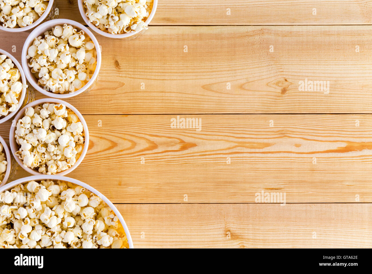 Movies background with various sized full popcorn bowls on table from top down perspective - Stock Image