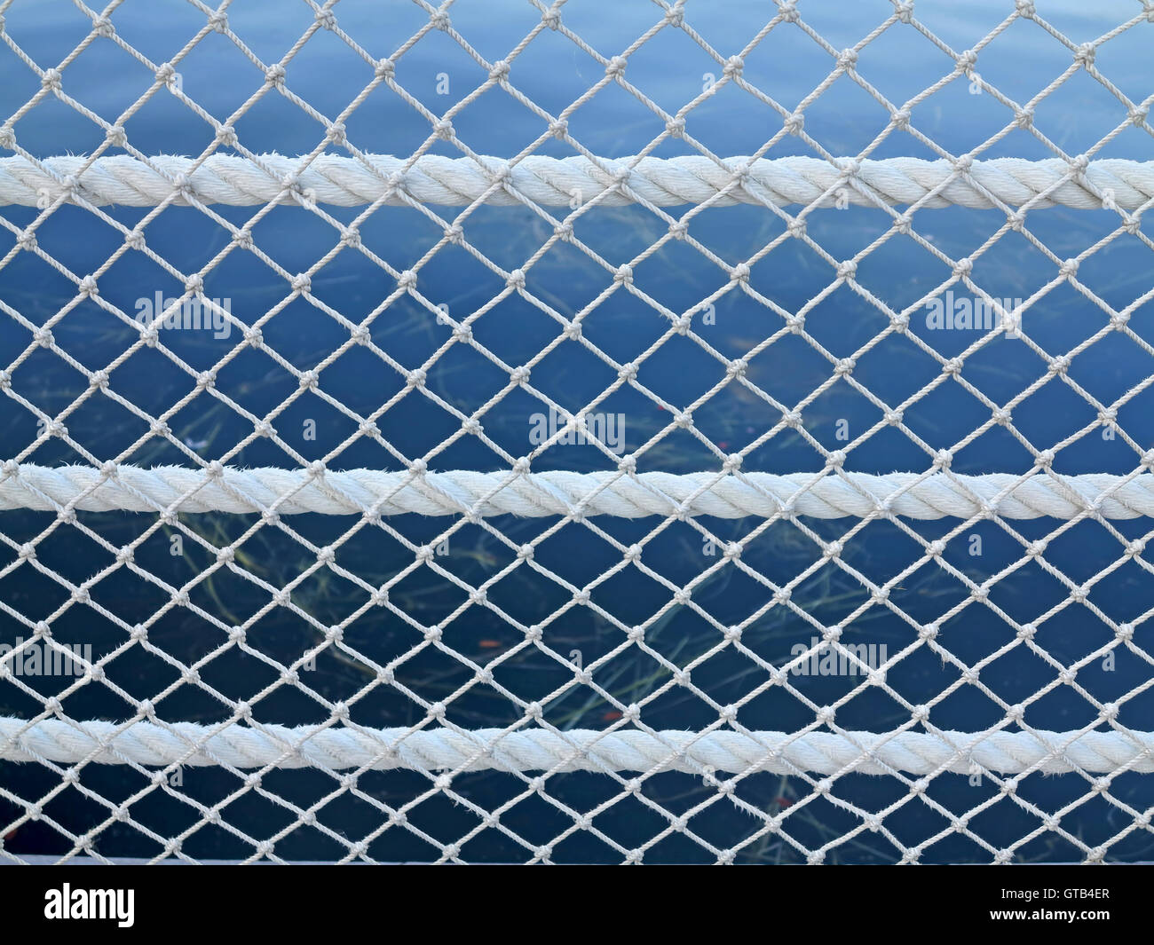 Rope and Net pattern with a lake behind - Stock Image