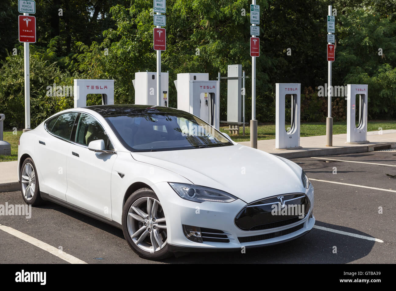 A Tesla Model S automobile gets a charge from a Tesla supercharger charging station at a highway rest stop. - Stock Image