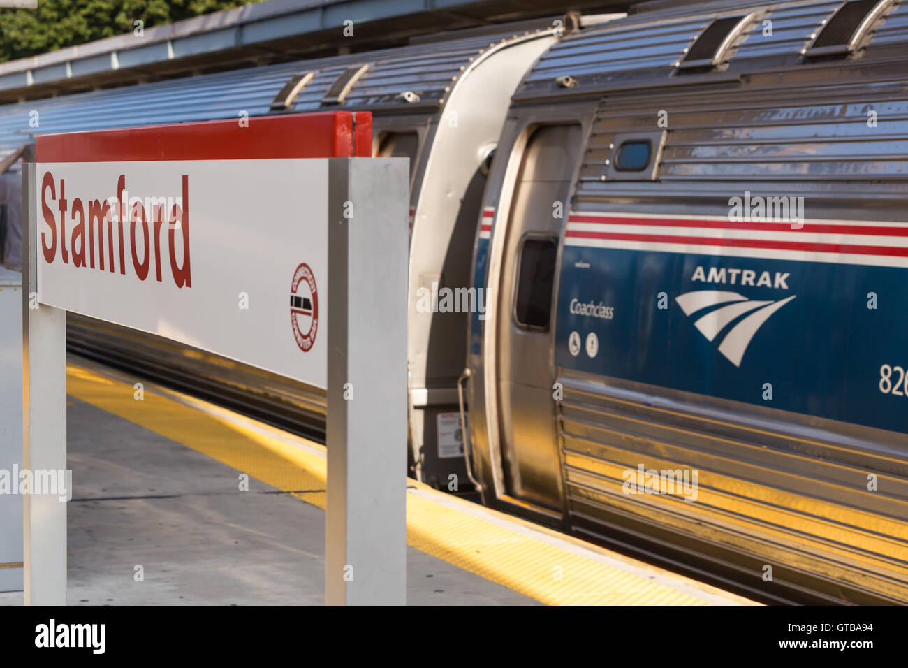 A northbound Amtrak Northeast Regional train picks up speed as it departs from Stamford Station in Stamford, Connecticut. - Stock Image