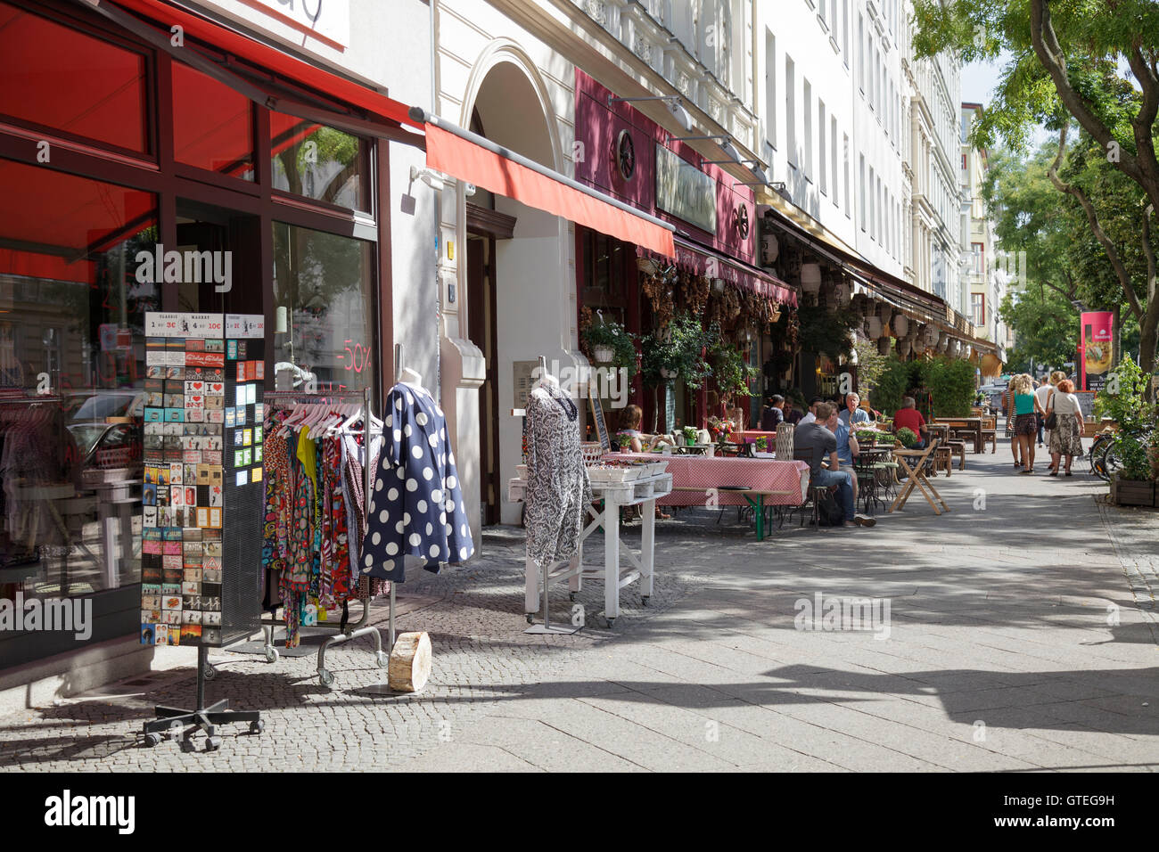 Bergmannstrasse in Kreuzberg people walking and sitting outside Knofi Feinkost Restaurant with clothing store, Berlin, - Stock Image