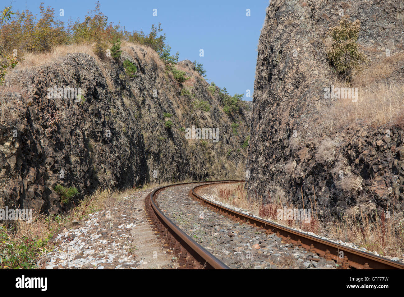 Curve of railway line passes through narrow rocky gorge. - Stock Image