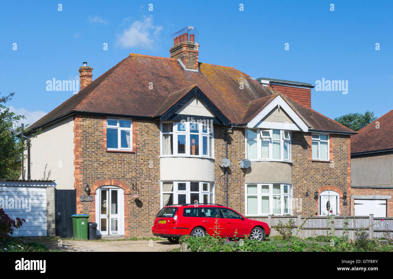 1930s typical British 2 floor semi detached brick house with bow windows and a sloping tiled roof, in Southern England, - Stock Image