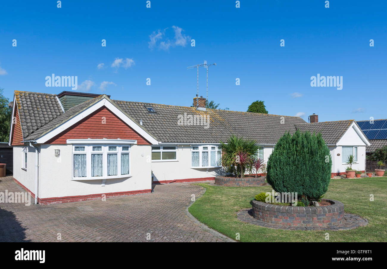 Small detached bungalow with a sloping tiled roof in the UK. - Stock Image