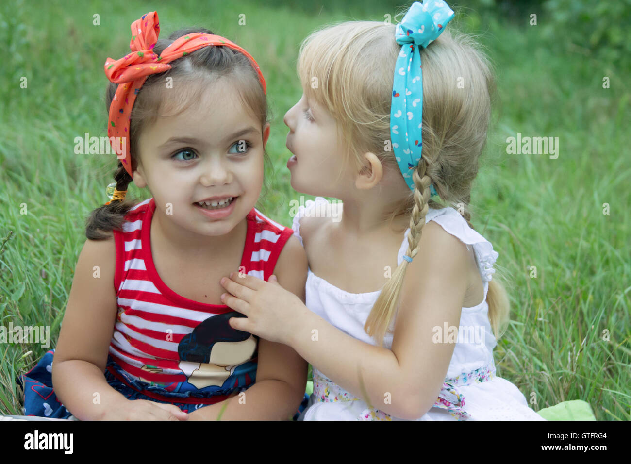 Two girls sharing secrets - Stock Image