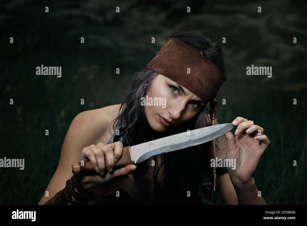 Dangerous gaze from indian hunter . Portrait with knife - Stock Image