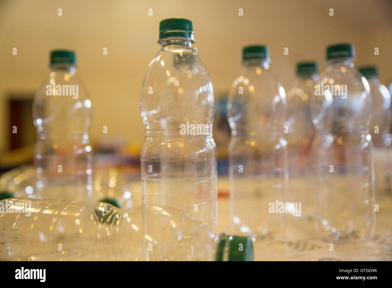 Transparent plastic water bottles standing on a table - Stock Image