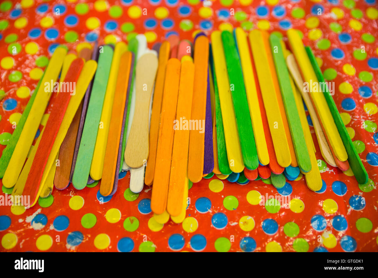 Lots of coloured lollipop sticks lying on a spotted tablecloth. - Stock Image