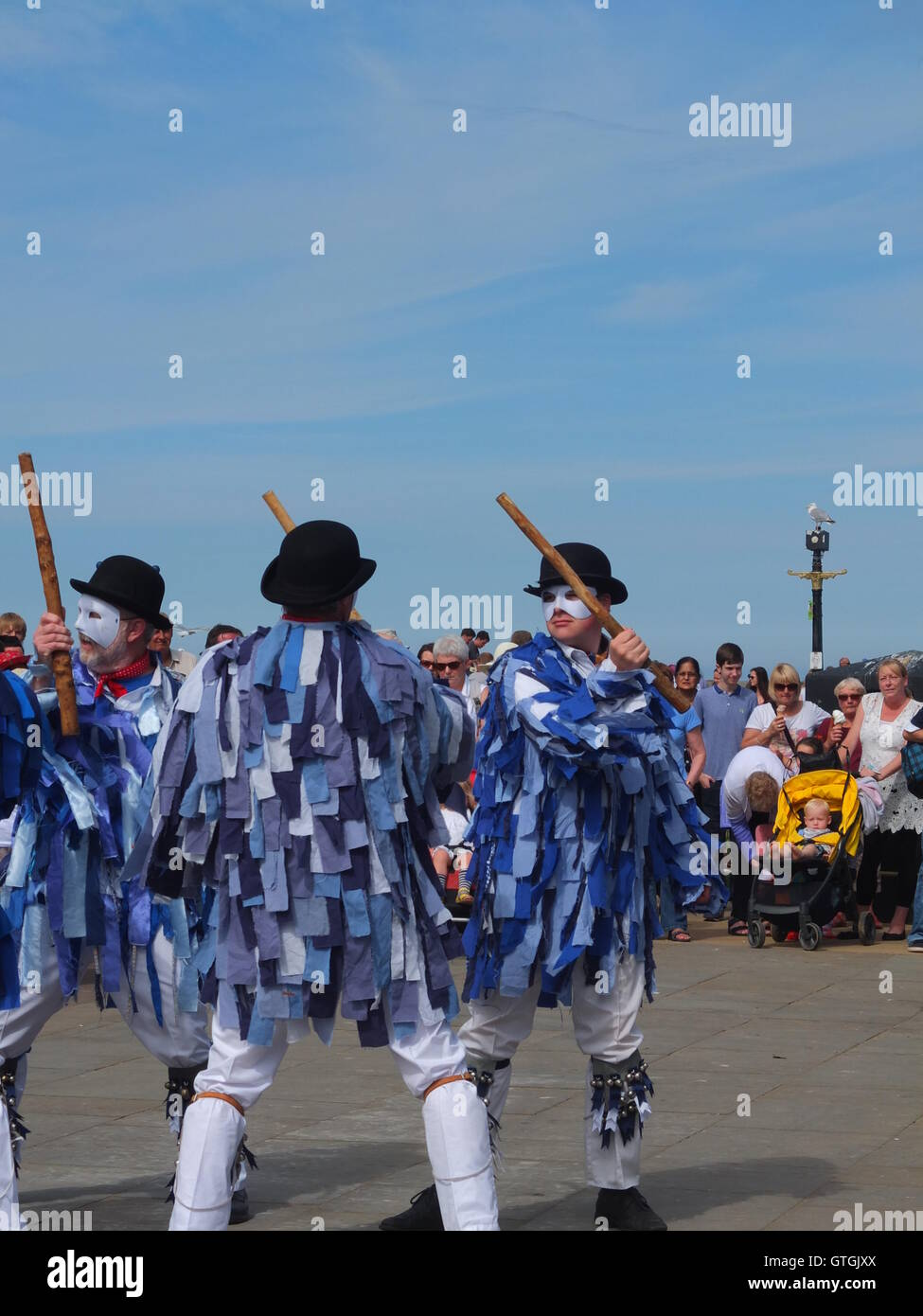 A crowd watch Hexham  Morris dancers performing on the quayside at Whitby Folk Festival 2016. Stock Photo