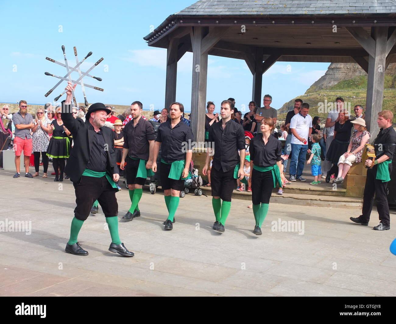 A crowd watch Four Corner Sword dancing troupe performing on the quayside at Whitby Folk Festival 2016. The 'lock' Stock Photo