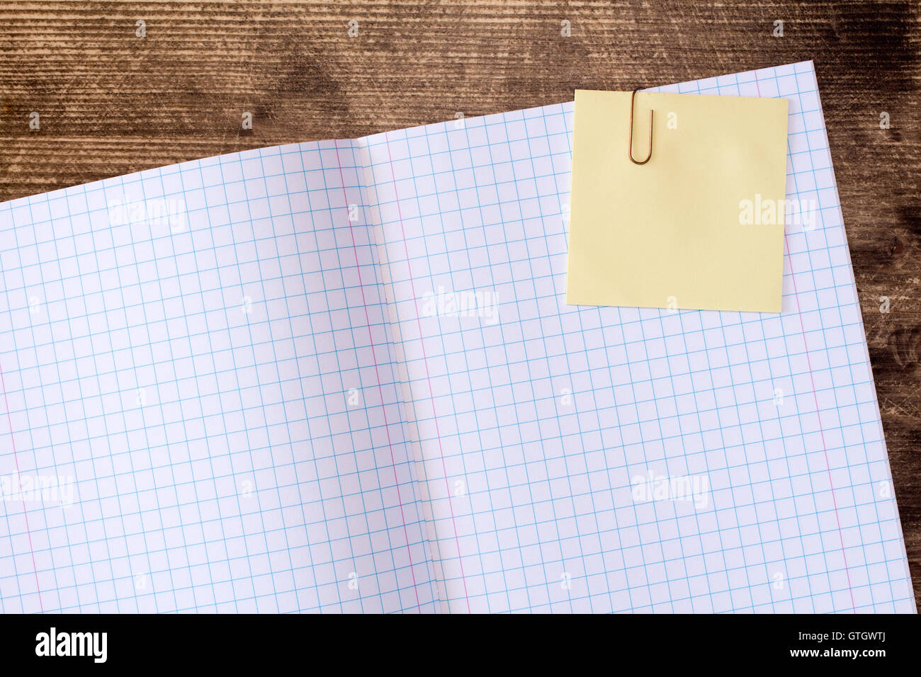 Squared exercise book with blank yellow sticky note - Stock Image