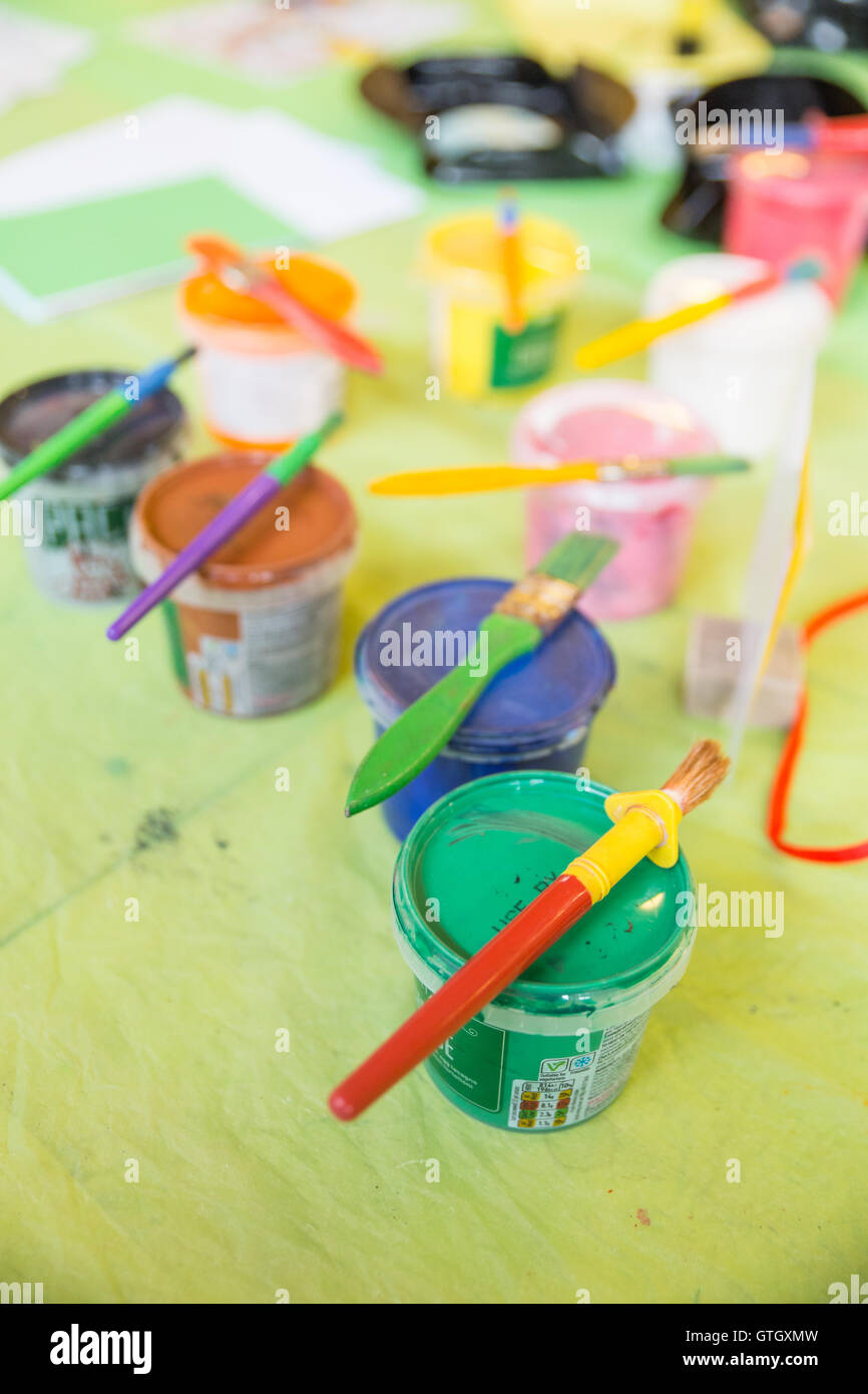 Pots of paint on a table with paintbrushes resting on top. - Stock Image