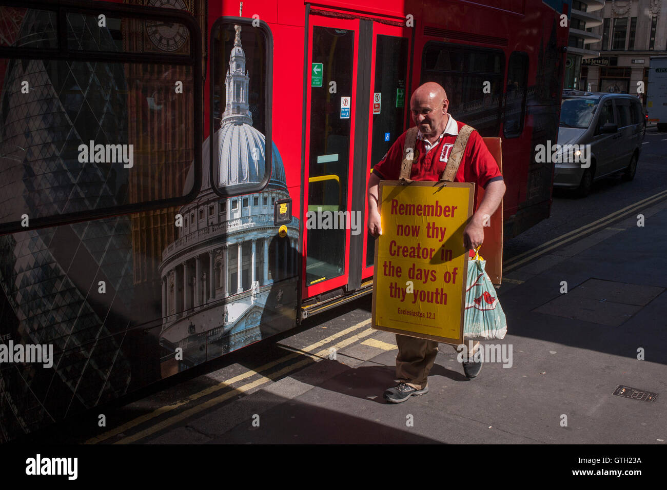 A Christian alongside a London tour bus carries a sandwich