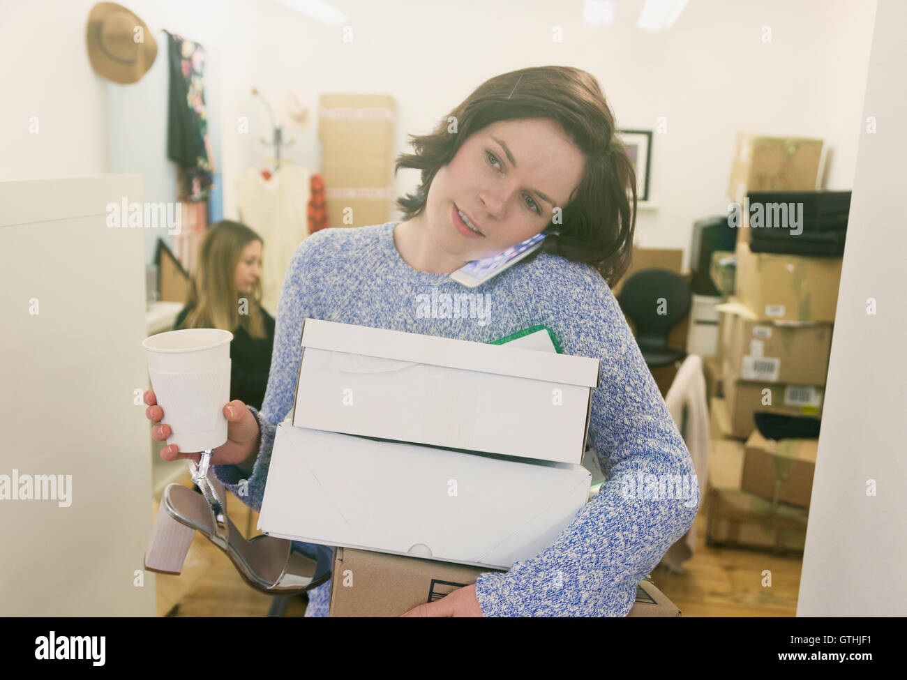 Fashion buyer multitasking carrying shoe boxes, coffee and talking on cell phone - Stock Image