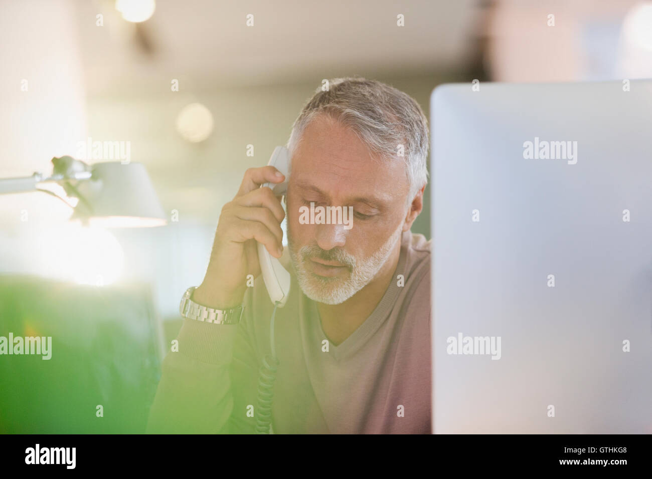 Businessman talking on telephone at computer in office - Stock Image