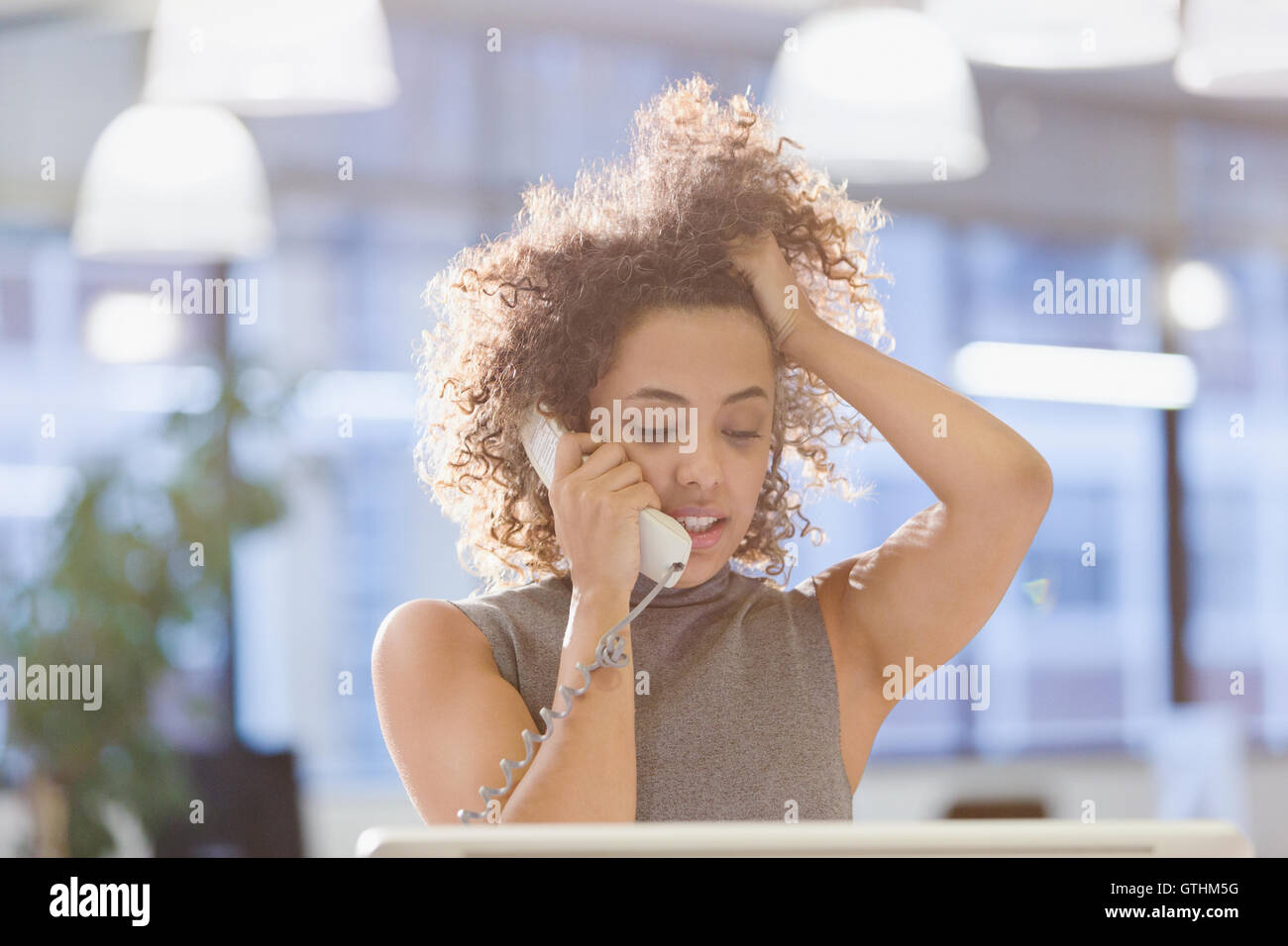 Businesswoman talking on telephone with hand in hair - Stock Image
