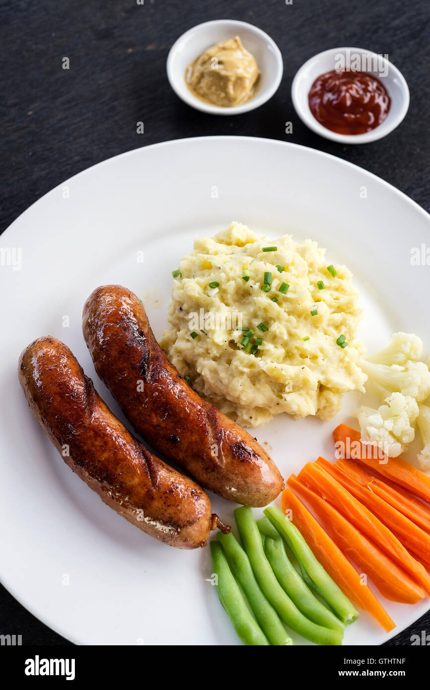 german sausage with mashed potato and vegetables simple meal - Stock Image