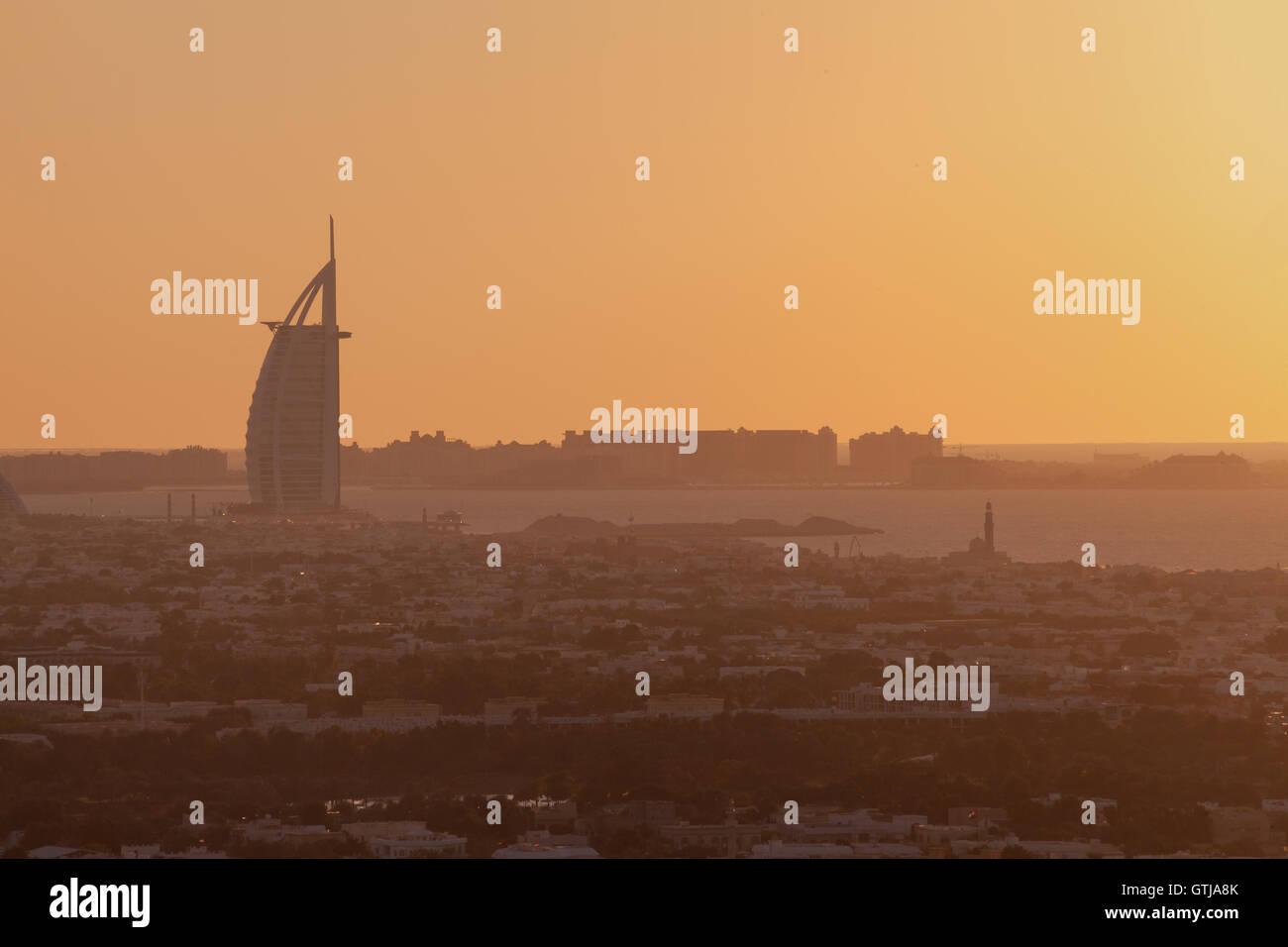 Burj Al Arab the luxury 7 stars hotel and jumeirah beach in panoramic orange silhouette sunset - Stock Image