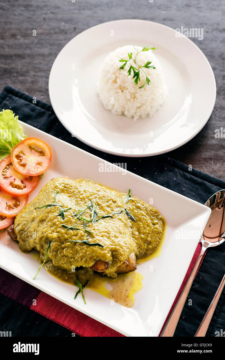 thai fish fillet with asian green curry sauce meal and rice - Stock Image
