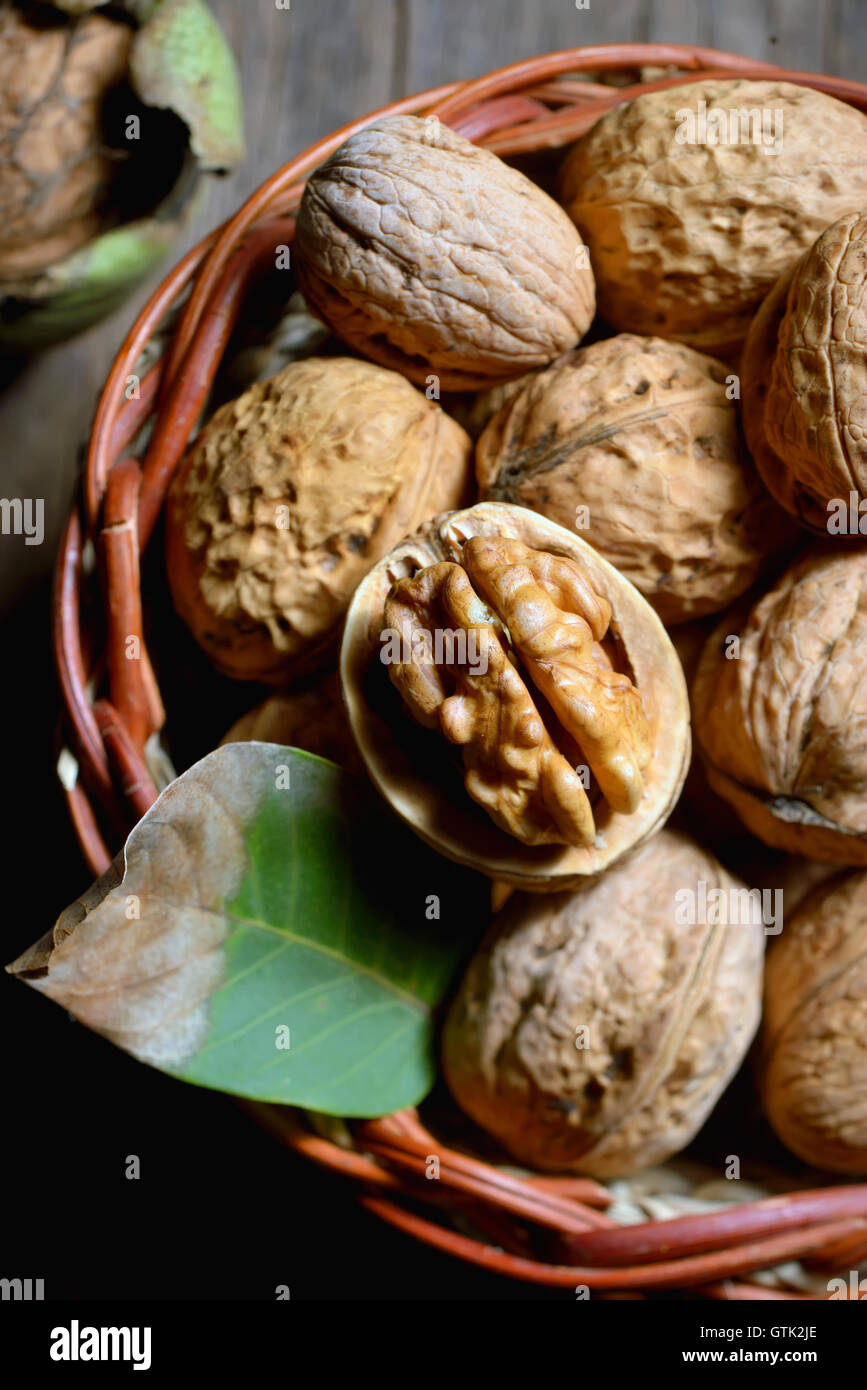 Walnut in basket and whole walnuts on rustic old wood - Stock Image