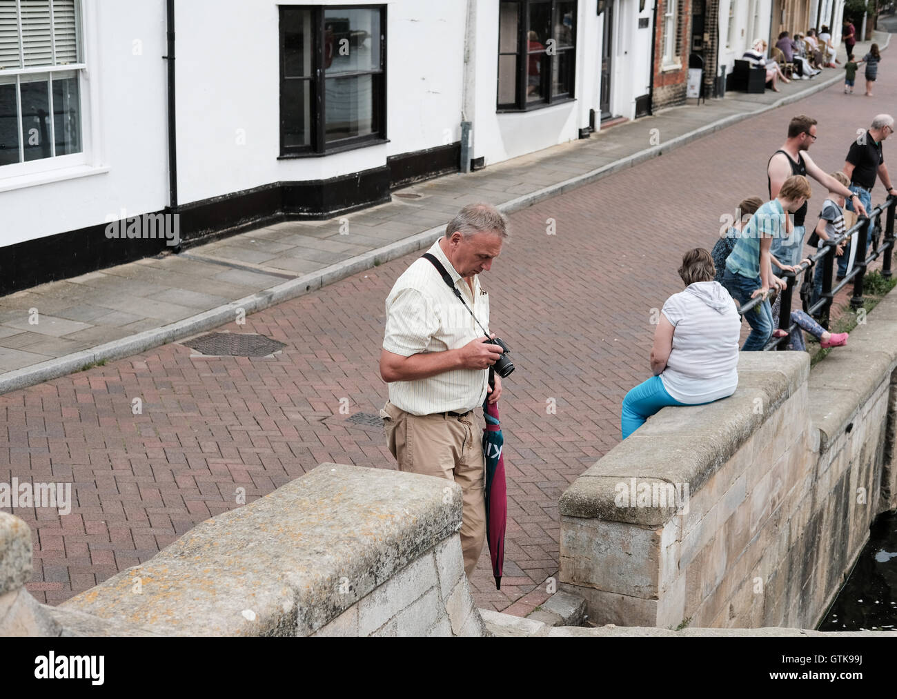 Amateur photographer seen with his camera at the market town of Saint Ives, Cambridgeshire during the summer. - Stock Image