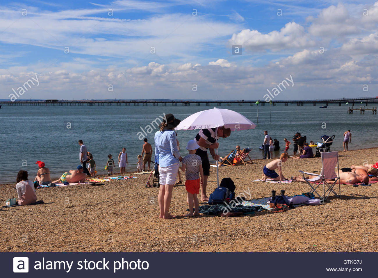 A family are on the busy Jubilee Beach in Southend-On-Sea, Essex. The father is pushing a parasol into the shingle - Stock Image