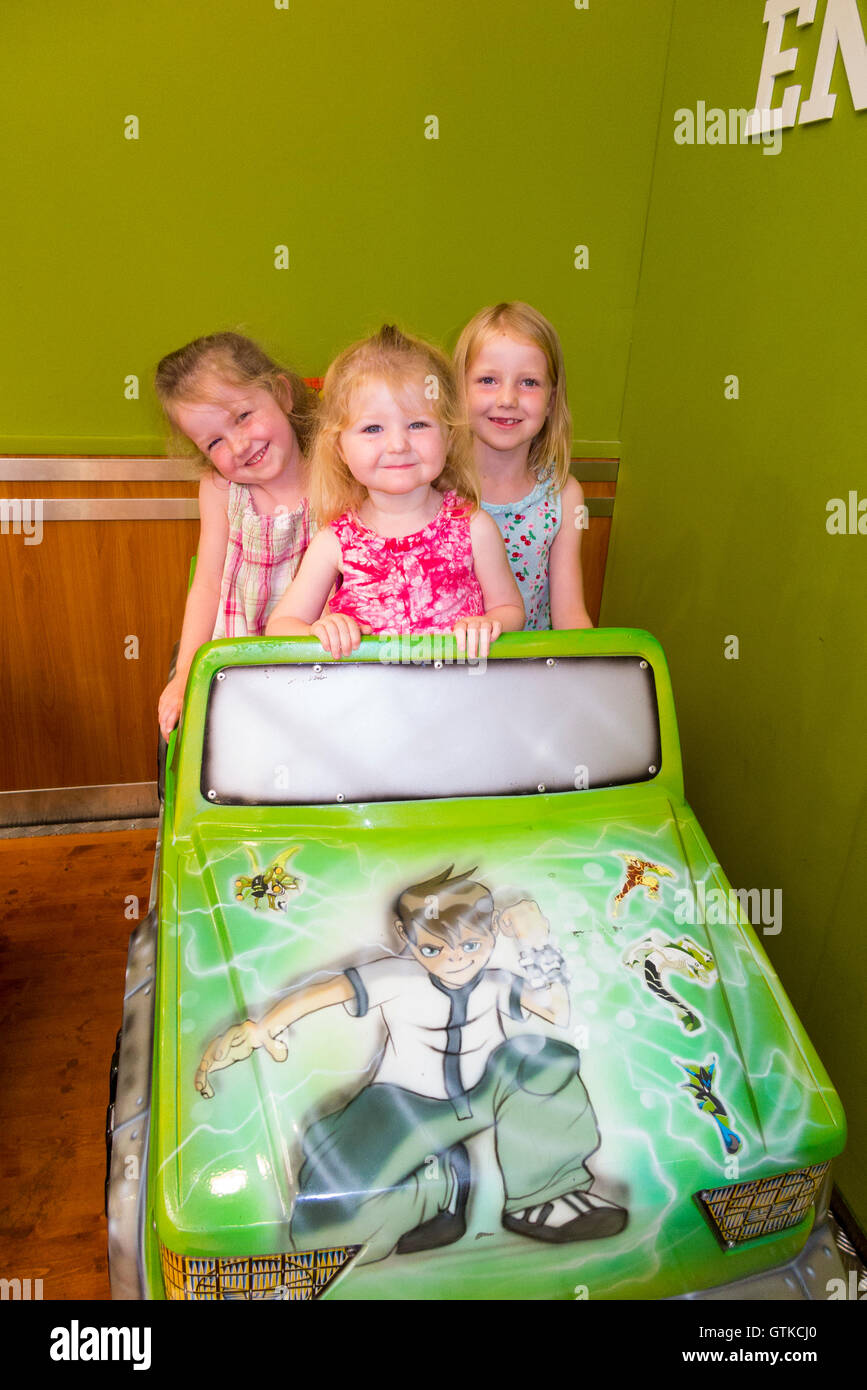 Three girls aged 2 4 6 yrs / young sisters / children / kids / girl enjoy coin operated child car ride in a shopping - Stock Image
