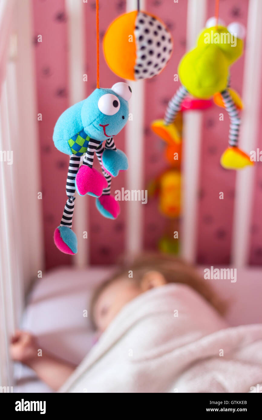 Baby bed with mobile toy above it; baby sleeping - Stock Image