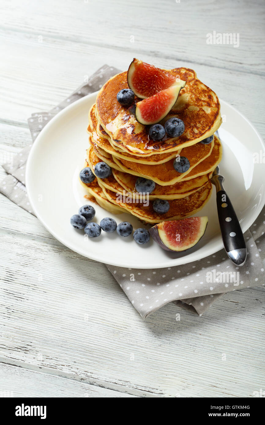 Pancakes with fruits on white wood, food closeup - Stock Image