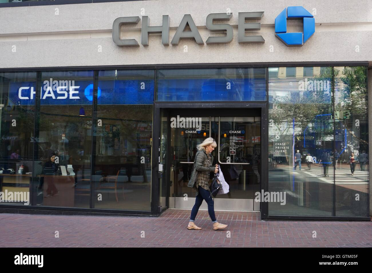 A woman walks by a Chase Bank storefront branch - Stock Image