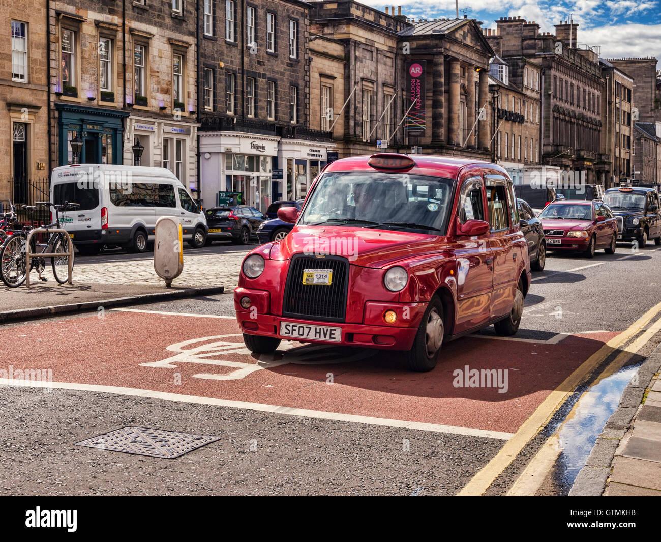 Red taxi cab in George Street, Edinburgh, Scotland, UK - Stock Image