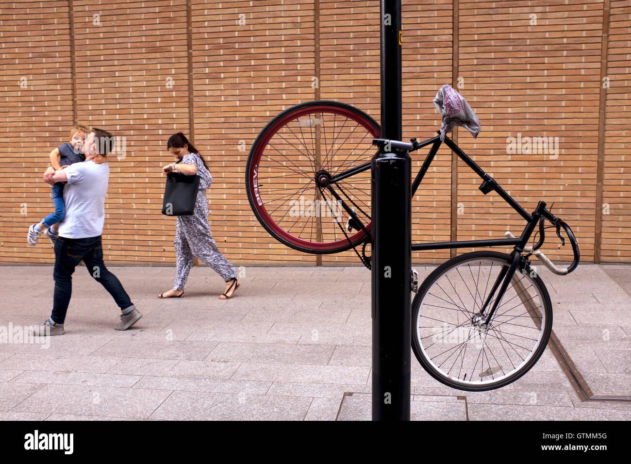 Bike chained to a lamp post, London Bridge, UK, United Kingdom - Stock Image